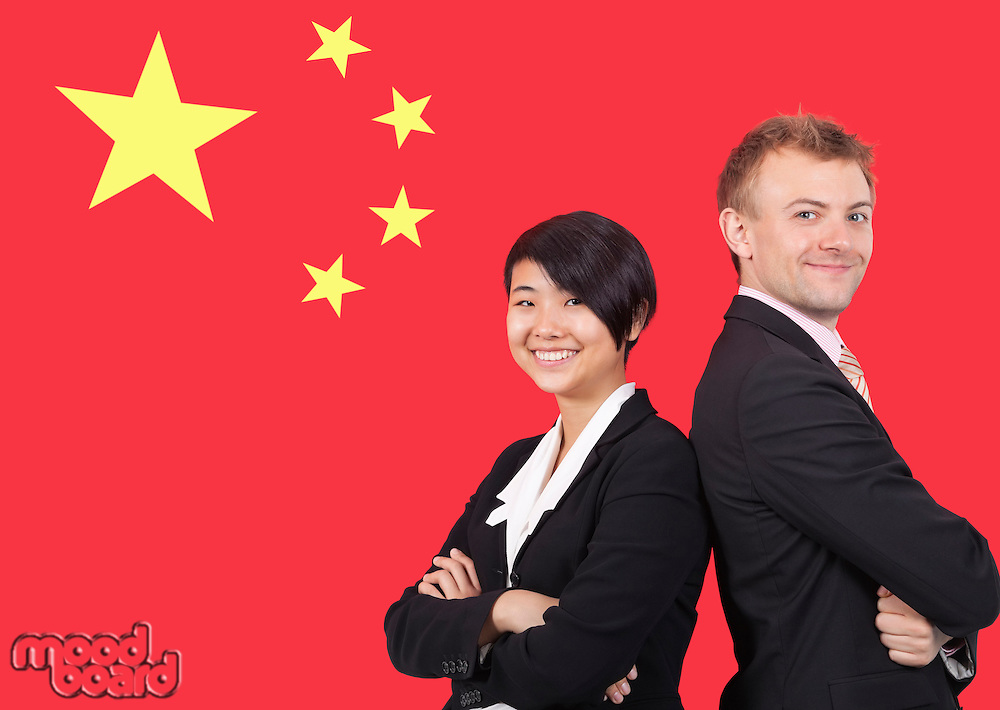 Portrait of young businesswoman and man smiling over Chinese flag