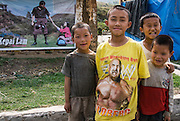 BHUTAN. A large poster advertising a Bhutanese movie, which appears to be a love story. There are 4 boys in the foreground. One boy is wearing a T shirt advertising a Western TV wrestling show.