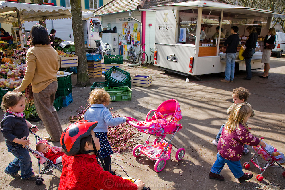 Customers wait for their orders at Marcus Dirr's stall at a bi-weekly market while children play, in the Wiehre Residential District of Freiburg im Breisgau, Germany.  (Marcus Dirr is featured in the book What I Eat: Around the World in 80 Diets.) Germans are among the biggest meat eaters in Europe, but eat slightly less meat than in decades past.
