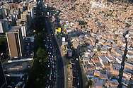 La vista aérea de las zonas marginales de la ciudad de Caracas. Muestra las miles de casas construidas cerro arriba. En medio, la autopista que divide el cerro de los edificios y las zonas residenciales.  Caracas, 19 - 09 - 2005 (Ramón Lepage / Orinoquiaphoto)  )   Aerial view the city of Caracas. The city with its Modern arquitecture, Highways and contrast between the rich and poor neighborhoods is surrounded by the Avila National Park and many hills around the valley where the shanty Towns or ´´barrios¨ have grown to become one the largest in Latin America.  (Ramón Lepage / Orinoquiaphoto)..