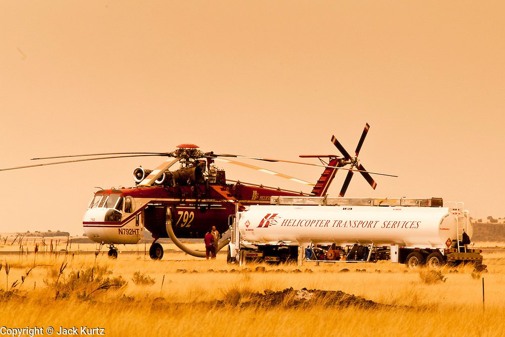 "04 JUNE 2011 - SPRINGERVILLE, AZ: Helicopters fighting the Wallow fire are refueling at the Springerville Airport. Smoke from the fire, more than 20 miles from Eagar, turned the sky bright orange. The fire grew to more than 140,000 acres early Saturday with zero containment. A ""Type I"" incident command team has taken command of the fire.  PHOTO BY JACK KURTZ"
