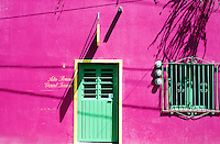 Green door with yellow trim contrasts sharply with purple wall, Ajijiic Mexico