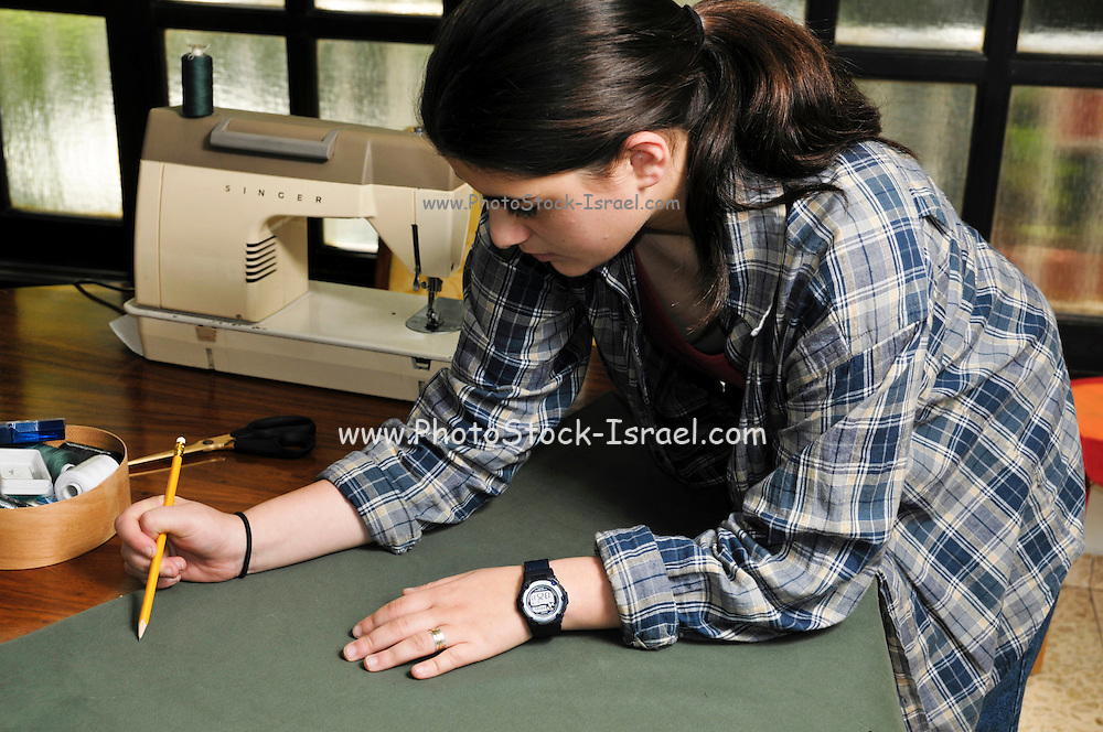Young female teen of fifteen sewing. Design stage, Marking the fabric before cutting Model release available