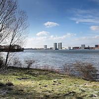 Nederland, Almere, 30 maart 2015.<br /> Rens Spanjaard initiator Weerwoud kijkt vanuit een toren op het eiland Utopia nabij Almere uit over het voedselbos.<br /> VOEDSELBOS OP UTOPIA<br /> We leggen een voedselbos aan op ons eiland. Van boom tot kruid en weer terug, alles is erop ingericht om een zo gezond en divers mogelijk bos neer te zetten dat zoveel mogelijk voedsel produceert. Wij zorgen ervoor dat je in 2022 kunt dwalen en verdwalen in een bos vol noten, appels, aardbeien en eindeloos veel ander lekkers. Om te plukken en van te genieten.<br /> Om in 2022 een voedselbos te hebben, planten we het nu al aan. Tijdens de Floriade is ons Weerwoud dan jong volwassen en vol in productie, en laat het je zien hoe een natuurlijk ecosysteem ons van voedsel kan voorzien.<br /> De Urban Greeners Rens en Koen zijn het tweespan achter het Weerwoud. Ze worden versterkt door twee voedselbosexperts van Food Forestry Nederland: Wouter Eck en Xavier San Giorgi. Ook zijn er studenten van CAH Vilentum die meedenken en helpen om er een leefbaar bos van te maken, door bijvoorbeeld onderzoek te doen.<br /> Op de foto: Het eiland Utopia met op de achtergrond Almere.<br /> Foto:Jean-Pierre Jans