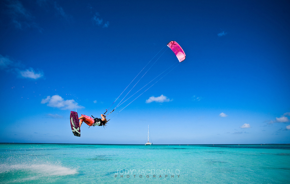Female kiteboarder flies over shallow clear waters in Barbuda, in the West Indies, Caribbean.