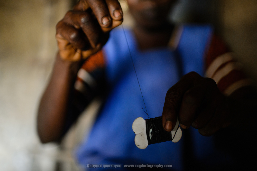 Traditional birth attendant, Antoinette Die Monti, in the village of Yapleu in western Cote d'Ivoire, shows a roll of thread of the type she would use to use to tie off newborn babies' umbilical cords in the years before the establishment of a local health centre that employs sterile practices.