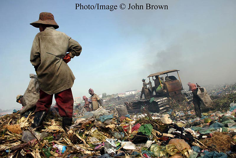 """A worker grasps a gaff while observing the work field at The Stung Meanchey Landfill in Phnom Penh, Cambodia. Over 700 tons of garbage is dumped there daily. She contributes to her family's income by scavenging for bottles, cans, and soft clear plastic. The sanitation dump, known as """"Smokey Mountain"""", is a source of air pollution that impacts the surrounding environment, and is well know for its poor sanitary conditions."""