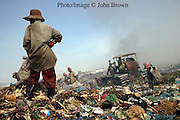 "A worker grasps a gaff while observing the work field at The Stung Meanchey Landfill in Phnom Penh, Cambodia. Over 700 tons of garbage is dumped there daily. She contributes to her family's income by scavenging for bottles, cans, and soft clear plastic. The sanitation dump, known as ""Smokey Mountain"", is a source of air pollution that impacts the surrounding environment, and is well know for its poor sanitary conditions."