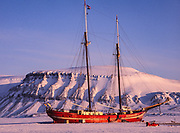 Dutch yacht Noorderlicht frozen into fjord, acts as hotel during winter months, huskies tethered outside as early warning protection against polar bears, taken during winter/spring ski crossing of Svalbard.