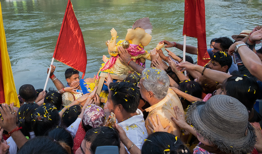Devotees do their best to touch a statue of Ganesha before it is given a bath in the river at the 6th Ganesha Festival at Utthyan Ganesha Temple, Nakhon Nayok, Thailand.