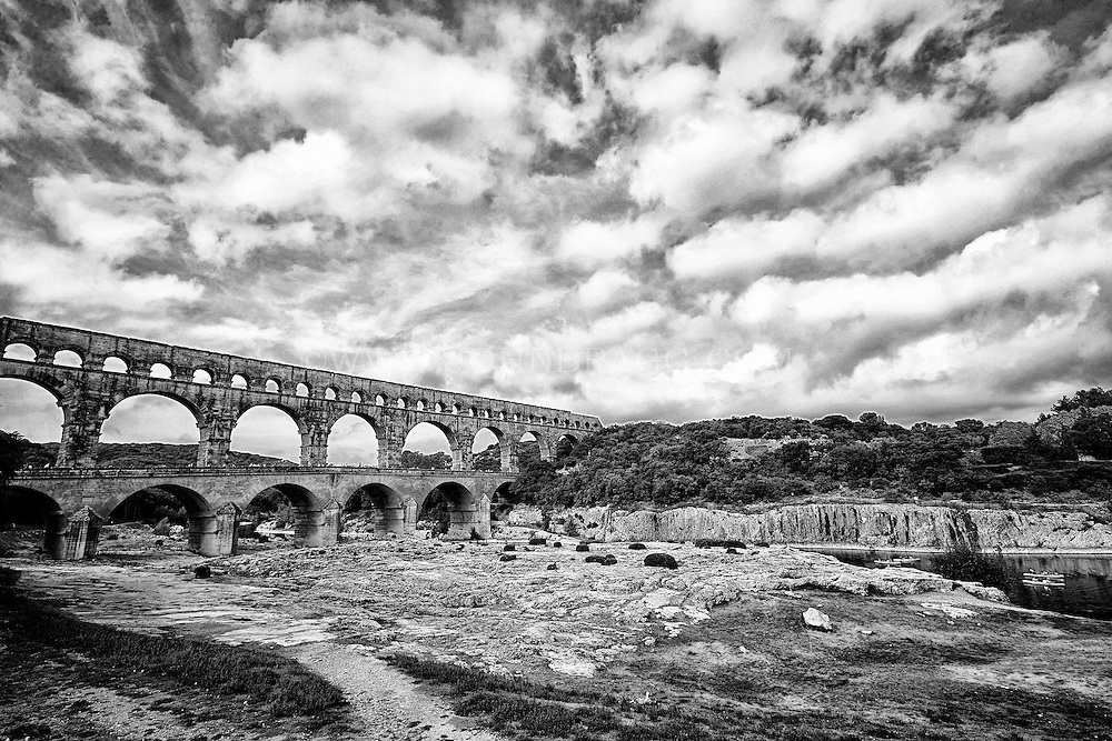 Black and white view of Pont du Gard (Roman Aqueduct), kayakers floating down the Gardon River, and Garrigue Natural Area, Vers-Pont-du-Gard, France.