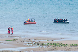 © Licensed to London News Pictures. 16/05/2020. Hastings, UK. Migrants are towed ashore at Pett Level near Hastings in East Sussex by the emergency services after crossing the English Channel earlier today in an inflatable boat. The group, possibly numbering up to 20 people including young children, were taken under tow by the Hastings Lifeboat and brought ashore by the Pett Level Independent Rescue Boat. They were met by coastguard and other government officials. Photo credit: Andrew Heather/LNP