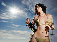 Woman in bikini holding champagne outdoors