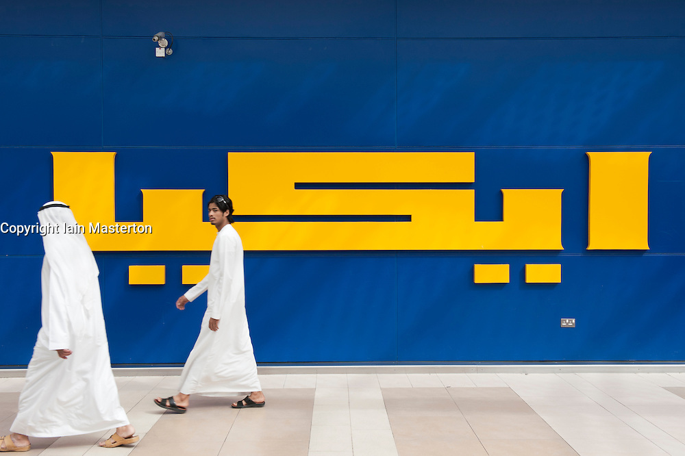 Arab men walking past sign for IKEA store in Dubai United Arab Emirates UAE