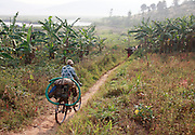 Man carrying water pump on the back of a bicycle. Village and Akagera river scenes, Kajevuba Village. Juru Sector. Bugesera district. Rwanda.<br /> <br /> &copy; Zute Lightfoot