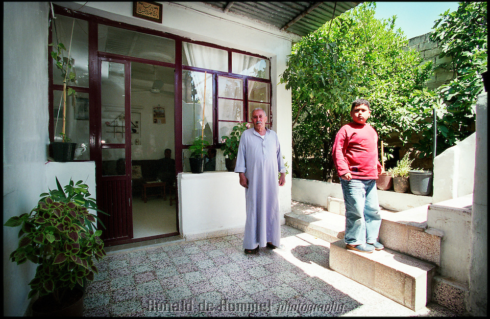 Ibrahim Omar Chair and his grandson in the courtyard of their home in northern Syria. The Palestinian refugee has lived here since 1948