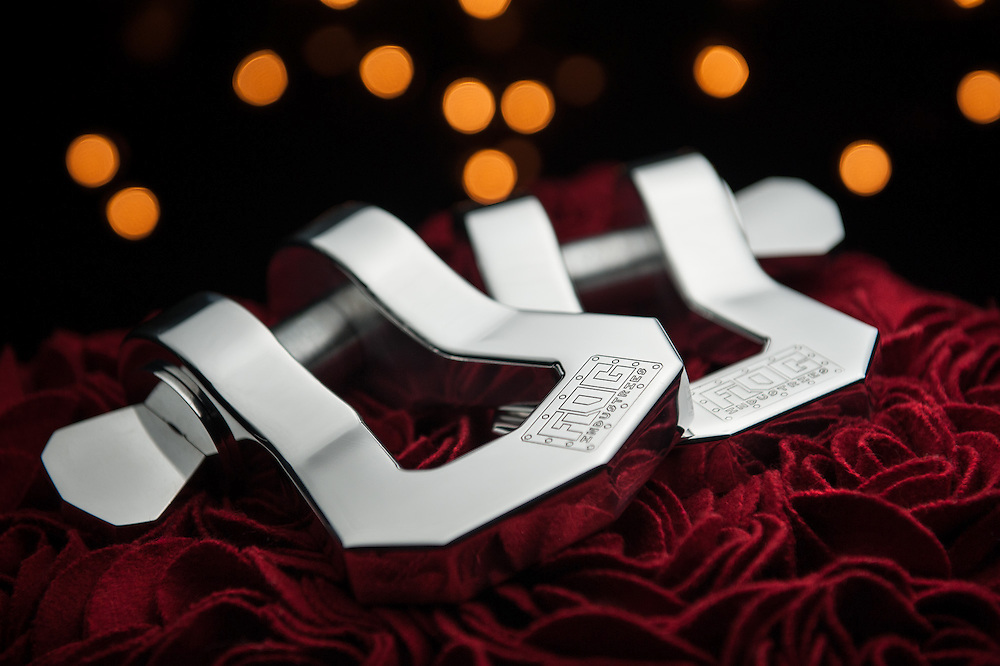 Product photography of product for Flog Industries. Julz tow hooks on a maroon background with bokah and light in the background.