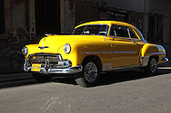 Yellow car in hard light in Havana Vedado, Cuba.