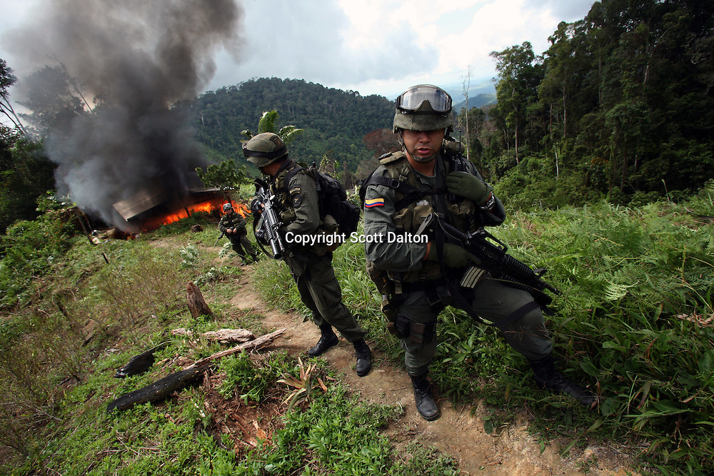 Members of the Jungla, a unit of the Colombian anti-narcotics police, keep watch after destroying a drug lab in a coca field in the Colombian state of Bolivar, on July 3, 2007. (Photo/Scott Dalton)