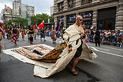 New York, NY - 25 June 2017. New York City Heritage of Pride March filled Fifth Avenue for hours with groups from the LGBT community and it's supporters. A man with a long robe made to look like Pacific Tapa, a bark cloth, marches with U.T.O.P.I.A., the United Territories of Pacific Islanders Alliance.