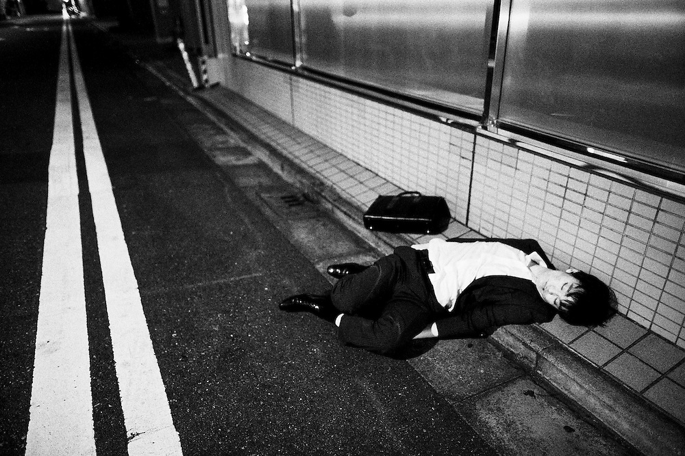 TOKYO, JAPAN - OCTOBER 23 : A drunk salaryman found lying on the road after passing out in Tokyo, Japan October 23, 2015.<br /> <br /> Richard Atrero de Guzman
