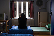 A female prisoner sitting on her bed in the first night  (4 person) dorm at HMP Holloway, the main womens prison in London.