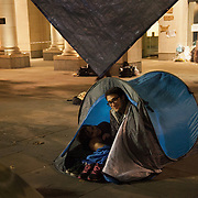 A couple settling in for the night. The London Stock Exchange was attempted occypied in solidarity with Occupy Wall in Street in New York and in protest againts the economic climate, blamed by many on the banks. Police managed to keep people away fro the Patornoster Sqaure and the Stcok Exchange and thousands of protestors stayid in St. Paul's Square, outside St Paul's Cathedral. Many camped getting ready to spend the night in the square.