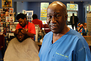 95788Staff Photo by Dan Henry / The Chattanooga Times Free Press- 7/18/14. Dr. Thomas Rumph stands in Big Boom's Barber Shop and Hair Salon on July 18, 2014 while speaking about plans to educate area children that they too can become black business owners. Dr. Rumph will exchange a free haircut for a child's attendance in a church service where black business owners will speak about how they achieved their dreams.