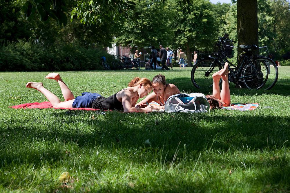 Nederland, Groningen, Noorderplantsoen. 14 juli 2010. Studenten studeren liggend in de zon. foto: Pepijn van den Broeke