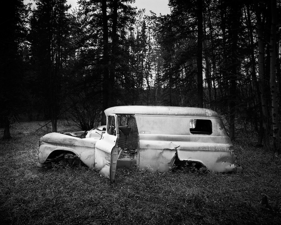 An old panel van lives in the woods right off the Alaska highway