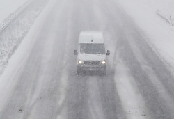 © Licensed to London News Pictures. 27/02/2018. New Hythe, UK.  A van drives on the M20 as snow falls. Freezing temperatures and heavy snow are affecting large parts of Kent.  Photo credit: Peter Macdiarmid/LNP
