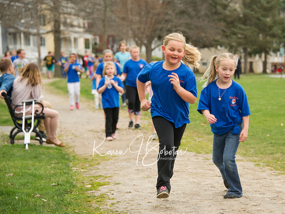 Elm Street School 1st graders Brooklyn and Catherine run laps around the loop at Leavitt Park during the school wide Tiger Trek on Friday morning.   (Karen Bobotas/for the Laconia Daily Sun)