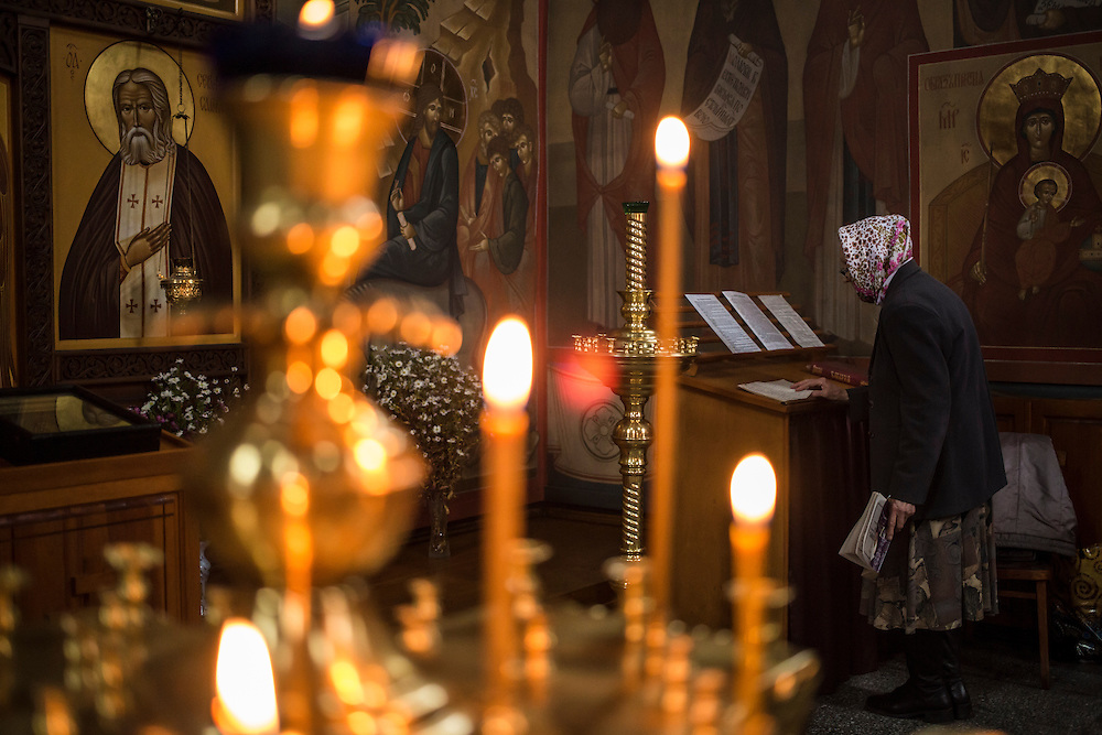 A woman prays in the local church on Saturday, October 26, 2013 in Baikalsk, Russia.
