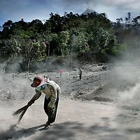 Indonesie.Jogjakarta.Juni 2006.<br /> Hulpverleners en locale mensen uit het natuurrampgebied rond Jogjakarta helpen mee de weg vrij te maken van lagen vulkaanas as gevolg van de recente vulkaanuitbarsting van de vulkaan de Merapi. (zie achtergrond).<br /> Foto:Jean-Pierre Jans