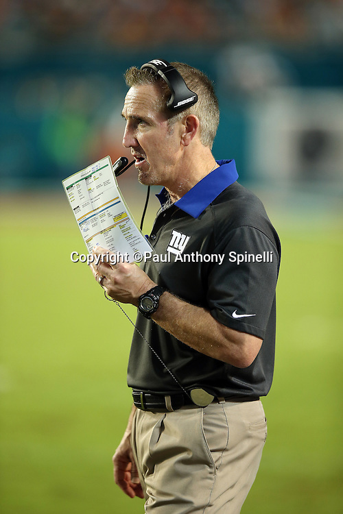 New York Giants defensive coordinator Steve Spagnuolo hides his mouth with his play chart as he calls a play on his headsets during the NFL week 14 regular season football game against the Miami Dolphins on Monday, Dec. 14, 2015 in Miami Gardens, Fla. The Giants won the game 31-24. (©Paul Anthony Spinelli)