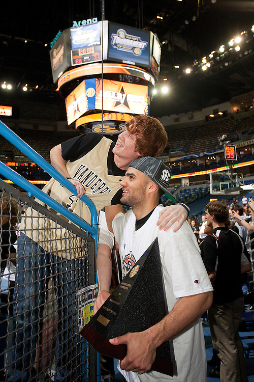 New Orleans , LA. - Game 11 of the 2012 SEC Men's Basketball Tournament between Kentucky and Vanderbilt, was played Sunday, March 11, 2012 at the New Orleans Arena. Vanderbilt forward Jeffery Taylor poses with the championship trophy and a fan after his team won the 2012 SEC Championship.