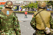 14 MAY 2010 - BANGKOK, THAILAND: An anti-government protester waves the Thai flag while Thai troops watch him Friday afternoon. Thai troops and anti government protesters clashed on Rama IV Road Friday afternoon in a series of running battles. Troops fired into the air and at protesters after protesters attacked the troops with rocket and small homemade explosives. Unlike similar confrontations in Bangkok, these protesters were not Red Shirts. Most of the protesters were residents of nearby Khlong Toei slum area, Bangkok's largest slum area. The running battle went on for at least two hours.   PHOTO BY JACK KURTZ
