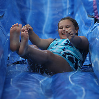 slides down one of four inflatable slides at the Tupelo Aquatic Center's Itty Bitty Beach Party Saturday