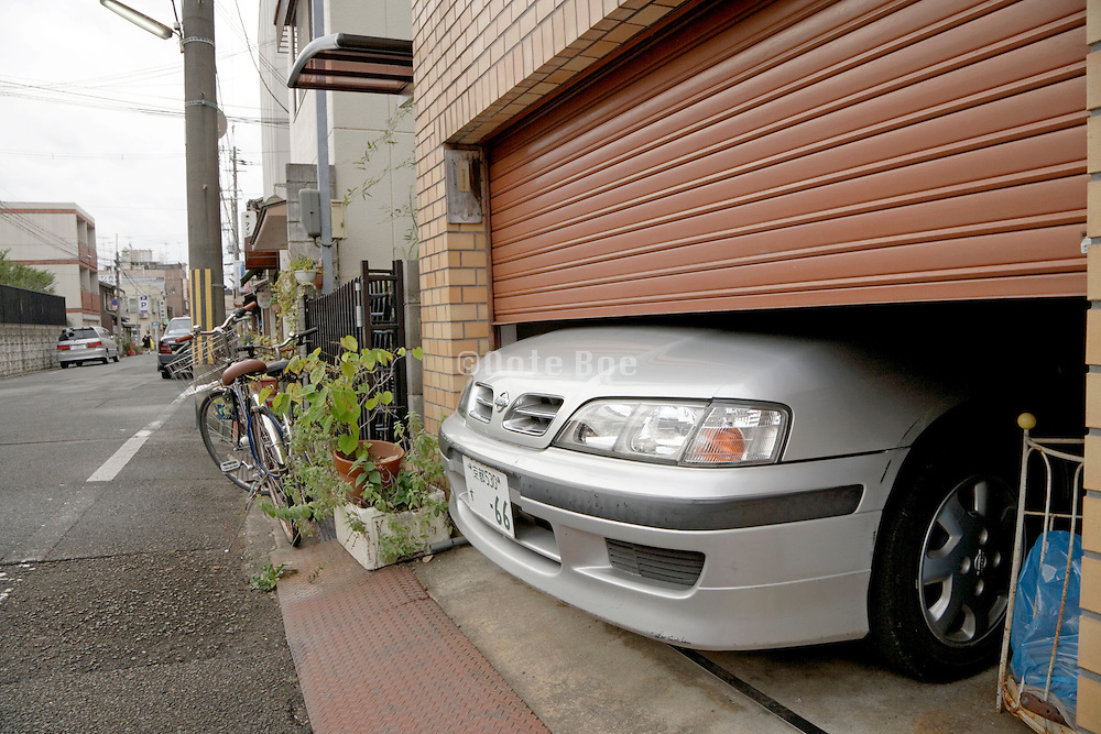 indoor parked car with nose sticking out from under the door as the car is bigger than the garage