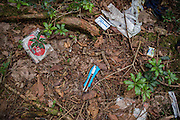 A variety of items are scattered on the ground in Aokigahara Jukai