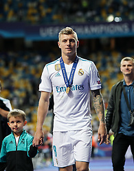 Toni Kroos of Real Madrid with his winner's medal  on the pitch as Real Madrid players celebrate winning the UEFA Champions League final football match between Liverpool and Real Madrid at the Olympic Stadium in Kiev, Ukraine on May 26, 2018. - Real Madrid defeated Liverpool 3-1. Photo by Andriy Yurchak / Sportida
