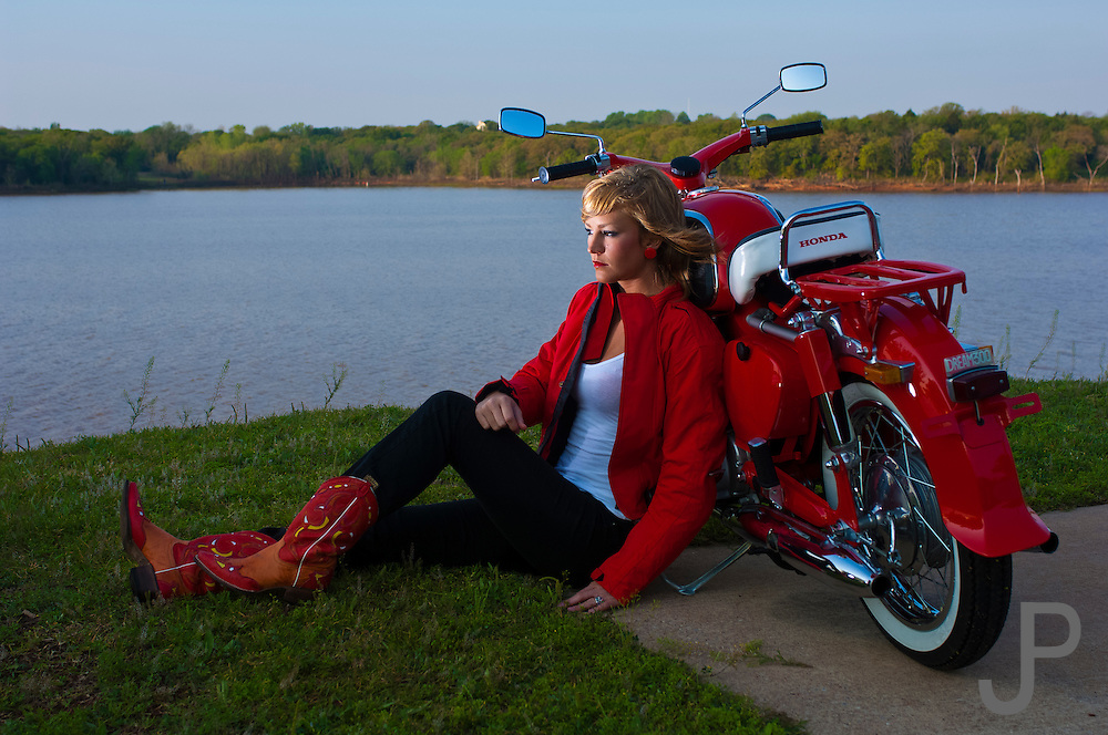 Model Mykie Oyler (model released) watching sunrise with her beautifully restored red 1960 Honda 305 Dream motorcycle (product released) at Arcadia Lake near Edmond, Oklahoma.