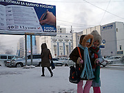 Kinder vor einer Plakatwand zur Duma Wahl von V. Putins Partei Einheitliches Russland in Jakutsk. Jakutsk hat 236.000 Einwohner (2005) und ist Hauptstadt der Teilrepublik Sacha (auch Jakutien genannt) im Foederationskreis Russisch-Fernost und liegt am Fluss Lena. Jakutsk ist im Winter eine der kaeltesten Grossstaedte weltweit mit bis zu durchschnittlichen Wintertemperaturen von -40.9 Grad Celsius.<br /> <br /> Children in front of a billboard of Vladimir Putins United Russia party for the Duma elections. Yakutsk is a city in the Russian Far East, located about 4 degrees (450 km) below the Arctic Circle. It is the capital of the Sakha (Yakutia) Republic (formerly the Yakut Autonomous Soviet Socialist Republic), Russia and a major port on the Lena River. Yakutsk is one of the coldest cities on earth, with winter temperatures averaging -40.9 degrees Celsius.