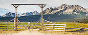 A ranch gate frames the Sawtooth Mountains near Stanley, Idaho, USA. A horse stands behind fencing. The Sawtooth Range (part of the Rocky Mountains) are made of pink granite of the 50 million year old Sawtooth batholith. Panorama stitched from 2 overlapping photos.