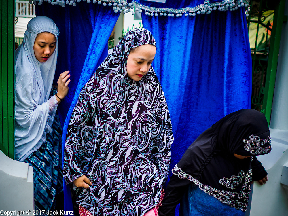 25 JUNE 2017 - BANGKOK, THAILAND: Women leave Bang Luang Mosque after Eid al-Fitr prayers. Eid al-Fitr is also called Feast of Breaking the Fast, the Sugar Feast, Bayram (Bajram), the Sweet Festival or Hari Raya Puasa and the Lesser Eid. It is an important Muslim religious holiday that marks the end of Ramadan, the Islamic holy month of fasting. Muslims are not allowed to fast on Eid. The holiday celebrates the conclusion of the 29 or 30 days of dawn-to-sunset fasting Muslims do during the month of Ramadan. Islam is the second largest religion in Thailand. Government sources say about 5% of Thais are Muslim, many in the Muslim community say the number is closer to 10%.    PHOTO BY JACK KURTZ