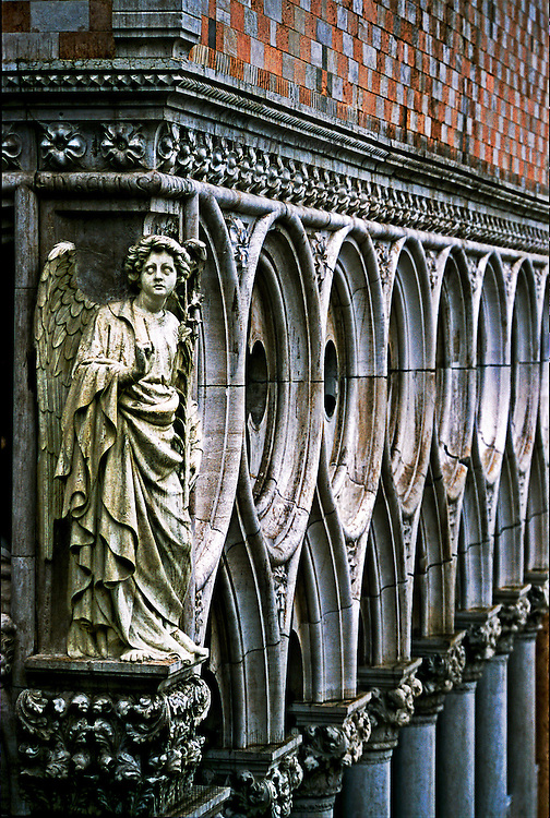 Sculpture of angel on the corner of the Doges' Palace colonnade, seen from roof of San Marco.  The angel, wearing richly folded drapery and wings,  looks frightened.  The upper part of the Gothic colonnade stretches away beyond.