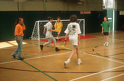 Group of young children playing game of football in sports hall with coach,