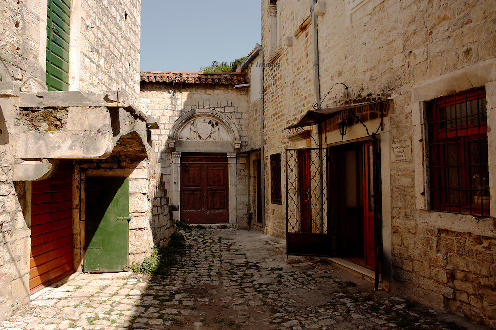 View down a medieval street in Trogir, Croatia.  Trogir is the best-preserved Romanesque-Gothic complex not only in the Adriatic, but in all of Central Europe. Trogir's medieval core, surrounded by walls, comprises a preserved castle and tower and a series of dwellings and palaces from the Romanesque, Gothic, Renaissance and Baroque periods. (Wikipedia) Though no people are present, there is nevertheless a sense that these ancient dwellings are still kept up and lived in.