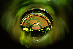 """Beauty at the Bottom: White Wine 1""- This image is a photograph of a wine bottle shot right down the mouth of the bottle. A television provides the main light source."