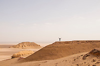 Putting the desert into perspective.  A figure atop a rocky ridge in the Egyptian desert beyond the Fayum oasis.